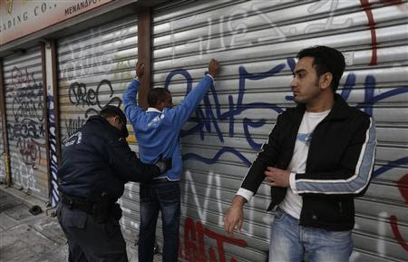 A police officer conducts a body search on an immigrant during an operation in the centre of Athens December 5, 2012. REUTERS-John Kolesidis