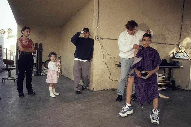 Juan the barber cutting Marcos' hair, Alley W. of Juniper St., by 108th St., LA