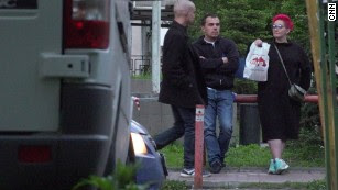 Anna Alimova offers a bag of syringes, bandages and ointments to a man leaving a 24-hour pharmacy.