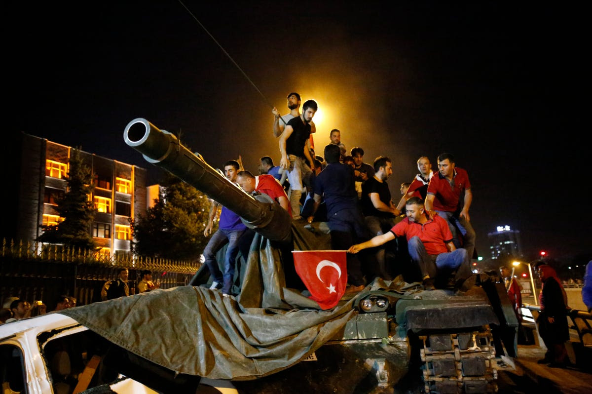 People stand on a Turkish army tank in Ankara.