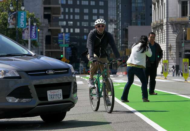 A Polk Street bicyclist has to steer past a car backing into a parking space and tourists snapping photos in the bike lane. Photo: Paul Chinn, The Chronicle