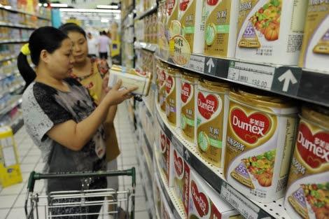 Una mujer mira una de las latas de leche Dumex en un supermercado de china.   Reuters