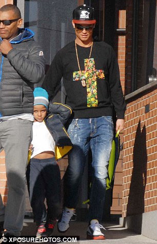 Ronaldo Jnr was wrapped up warm as he made his way home from school on Monday