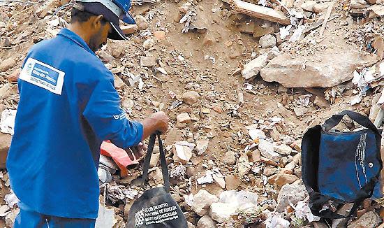 Funcionário de empresa que trabalha em construção de museu vasculha bolsa no meio de entulho retirado de prédios