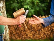 Un homme remettant ldes outils de jardinage à un autre homme