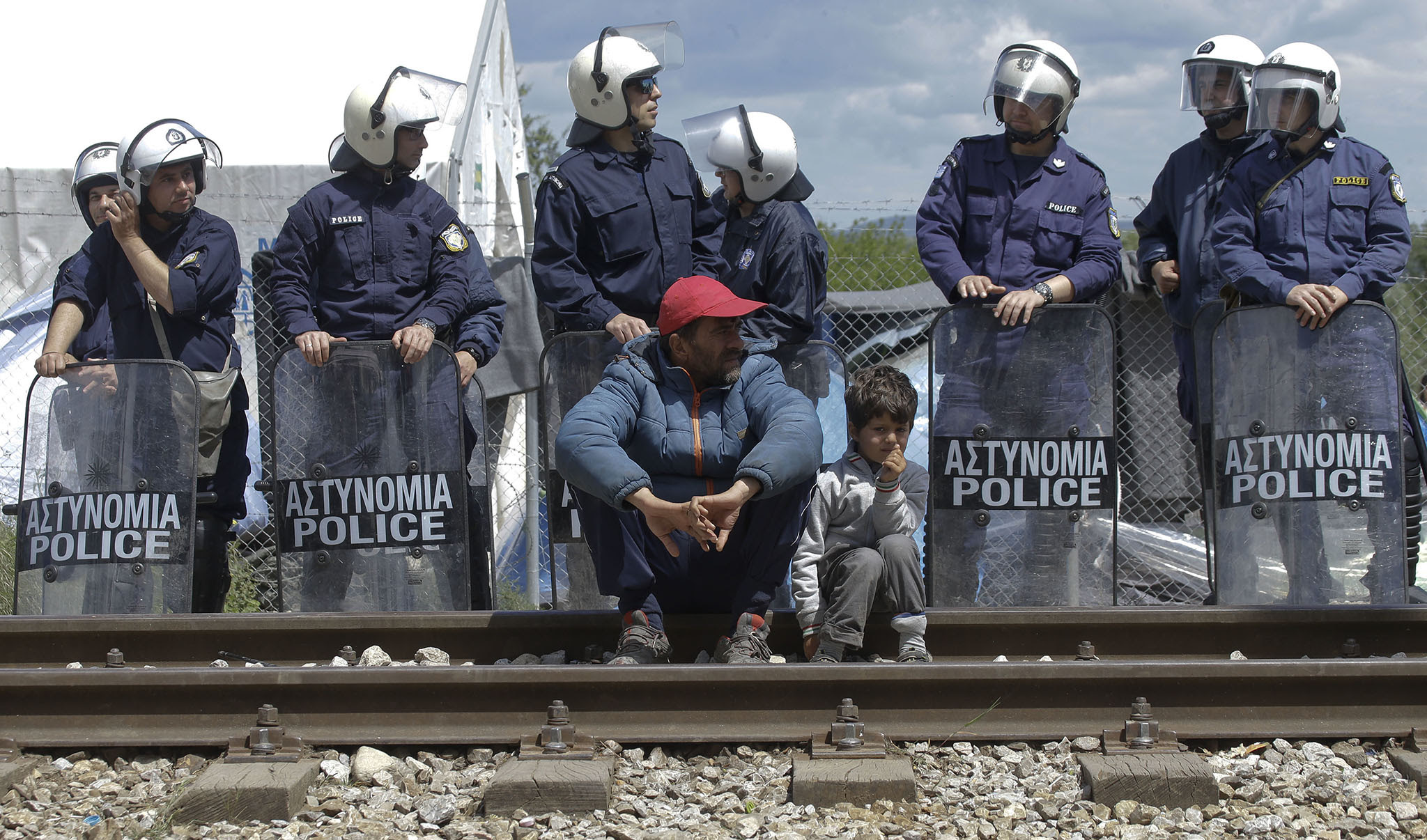 A child and a man sit on the tracks in front of Greek policemen in riot gear during a protest at the northern Greek border point of Idomeni, Greece