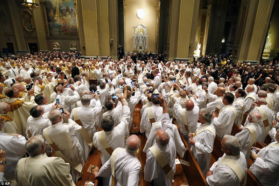 Pope Francis, center, walks though a great crowd of people toward the altar at Cathedral Basilica of Sts Peter and Paul to start a mass