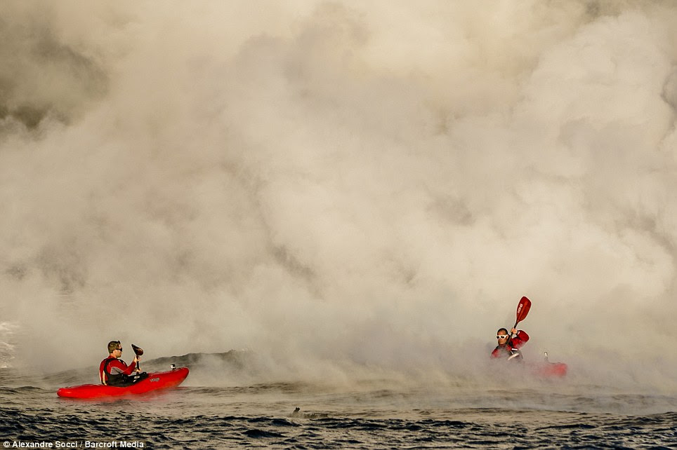 Courage: Pedro Oliva and Ben Stookesberry are immersed in steam as they paddle feet from molten lava flows in Kauai, Hawaii