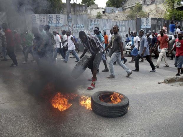 Manifestante coloca fogo em pneu durante protesto nesta sexta-feira (22) contra o processo eleitoral em Porto Príncipe, no Haiti (Foto: REUTERS/Andres Martinez Casares)
