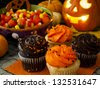 Halloween cupcakes with orange and black icing on orange napkin. - stock photo