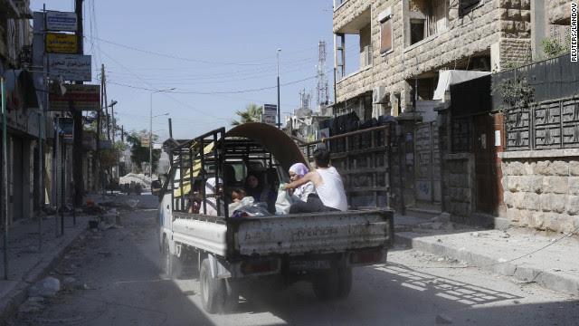 Escaping civilians drive through the El Amreeyeh neighborhood in Aleppo.
