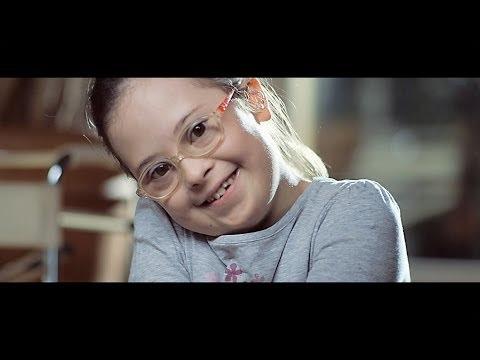 menina com síndrome de down sorri para a câmera.