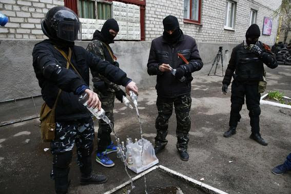 Masked men empty bottles of vodka to use them for petrol bombs in front of police headquarters in Slaviansk, April 12, 2014. REUTERS-Gleb Garanich