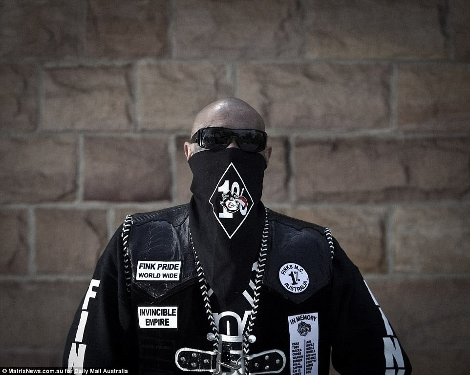 A member with his heavily tattooed face hidden under dark glasses and a Fink-branded scarf