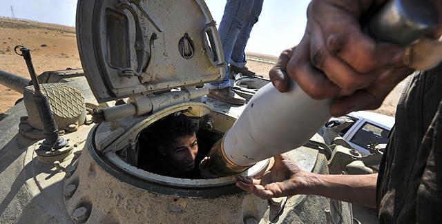 Un rebelde libio en un tanque de las fuerzas de Gadafi, cerca de la ciudad de Ajdabiya. | AFP MÁS FOTOS