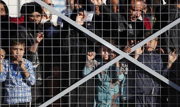 Migrants behind wire mesh