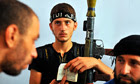 A Syrian rebel holds a Qur'an and a rocket-propelled grenade in an Aleppo school