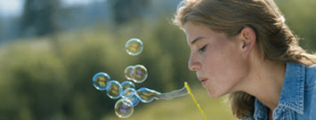 Photo: Young woman blowing bubbles.