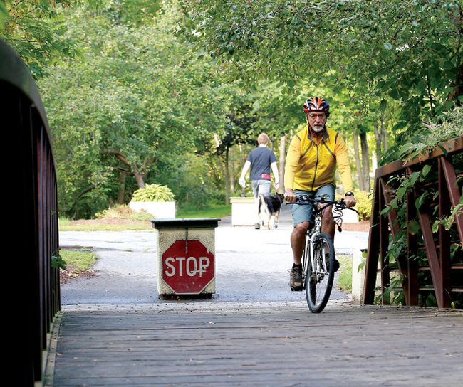 Alan Medcalf rides across a bridge on the Brock Trail over Buell's Creek at Beecher Street in this file photo. (DARCY CHEEK/The Recorder and Times)