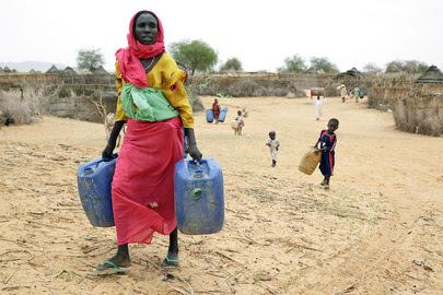 Uma mulher caminha para o local de distribuição de água em Tora, norte de Darfur, 2009 (ONU/Olivier Chassot)