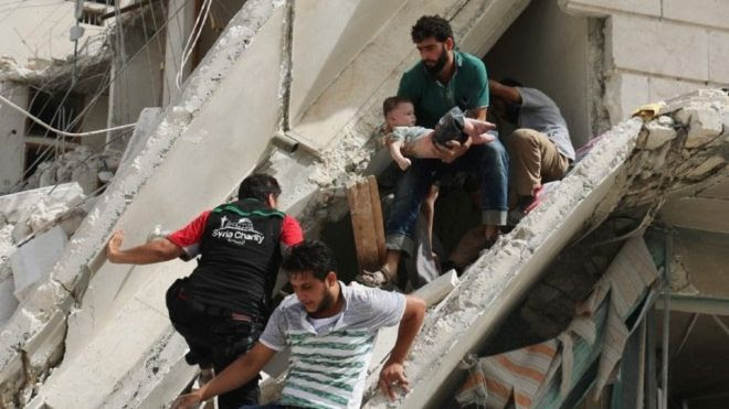 Syrian men remove a baby from the rubble of a destroyed building following a reported air strike in the Qatarji neighbourhood of the northern city of Aleppo (September 21, 2016)