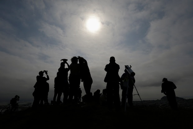 A crowd watches the solar eclipse from Bernal Heights Hill in San Francisco, Monday, Aug. 21, 2017. (AP Photo/Jeff Chiu)