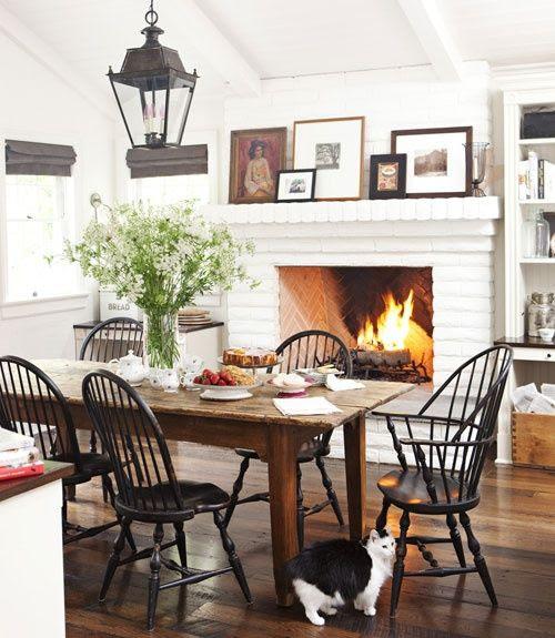 .Cozy dining room layered artwork, lantern, Windsor chairs.