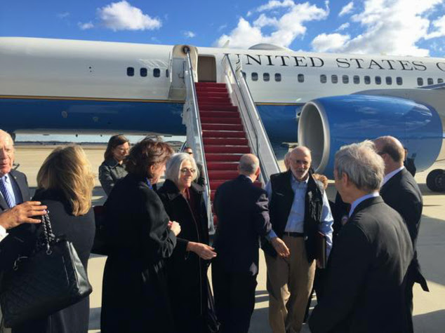 Alan Gross arrived Wednesday at Andrews Air Force Base in Maryland. The U.S. and Cuba have agreed to re-establish diplomatic relations and open economic and travel ties, marking a historic shift in U.S. policy toward the communist island after a half-century of enmity dating back to the Cold War, American officials said Wednesday. The announcement came amid a series of sudden confidence-building measures between the longtime foes, including the release of American prisoner Alan Gross, as well as a swap for a U.S. intelligence asset held in Cuba and the freeing of three Cubans jailed in the U.S. Gross' wife Judy is at center. (AP Photo/Sen. Jeff Flake)