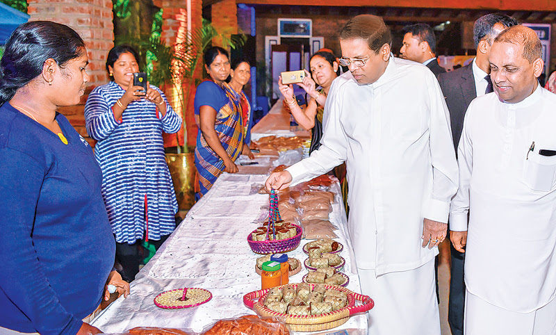 President Maithripala Sirisena and Agriculture Minister Mahinda Amaraweera yesterday, inspecting a stall producing indigenous food items from around the country at an event held at BMICH to mark World Food Day. Picture by Chandana Perera