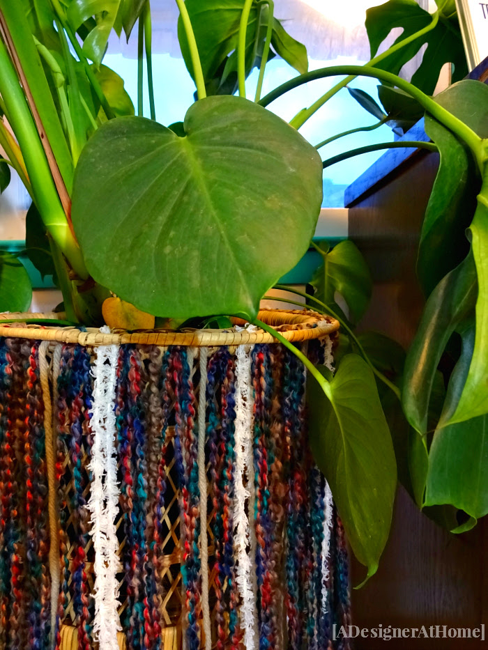 split leaf pothos in wicker plant stand with diy yarn fringe skirt