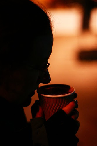 Silhouette profile of a person's face, sipping from a cardboard cup of steaming hot chocolate which they are holding with both hands