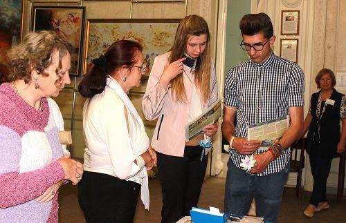 图5:观看画展后,许多民众与学员交谈,了解更多关于法轮功的真相。