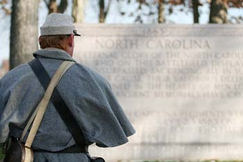 A North Carolina reenactor pauses to think about the soldier he is portraying by the North Carolina Memorial during Remembrance Day in Gettysburg, PA.  © Mike Lynaugh