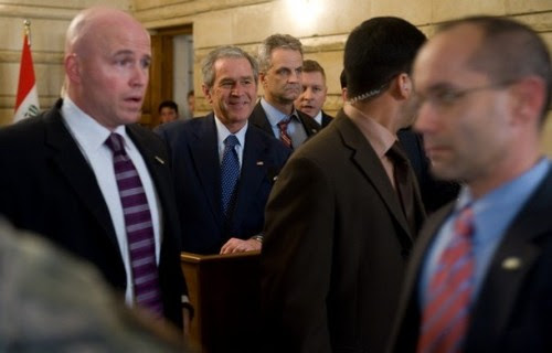 US President George W. Bush(2ndL), surrounded by security personnel, smiles after an Iraqi man threw his shoes at Bush during a joint press conference with Iraq's Prime Minister Nuri al-Maliki at Maliki's private office during an unannounced visit to Baghdad, Iraq, on December 14, 2008. The trip marks Bush's fourth visit to the country during his presidency. AFP PHOTO / Saul LOEB (Photo credit should read SAUL LOEB/AFP/Getty Images)