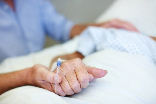 Close-up of a younger person holding an the hand of an elderly person with an IV drip.