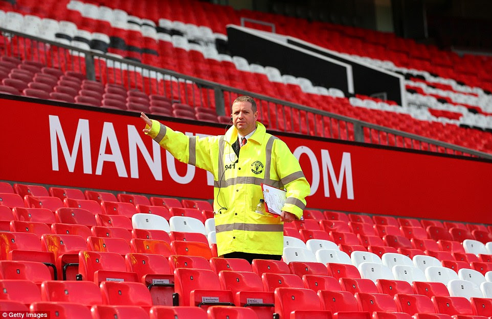 A steward evacuates fans from the ground prior to the Premier League match between Manchester United and Bournemouth at Old Trafford