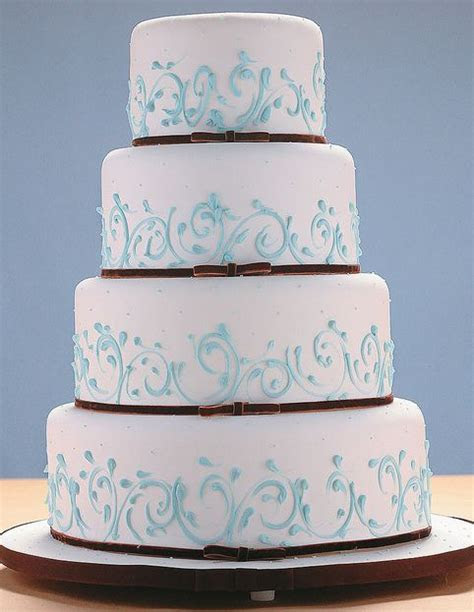 Four tier round white wedding cake with thin brown bands