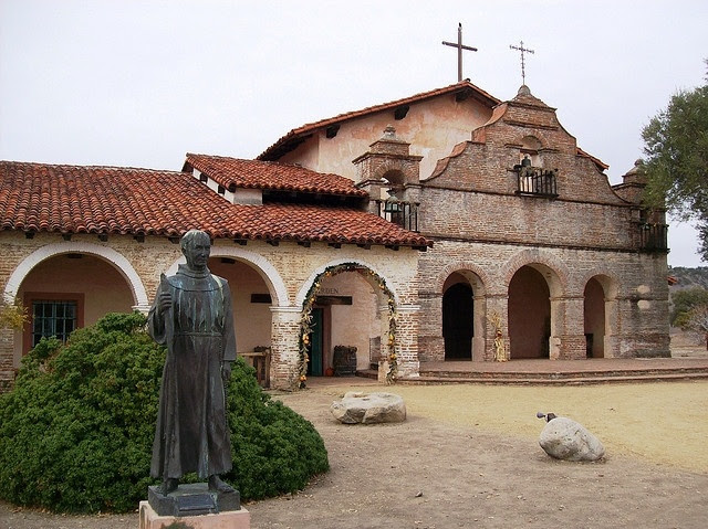 Mission San Antonio de Padua, Monterey County, CA with the statue of Father Junipero Serra outside.