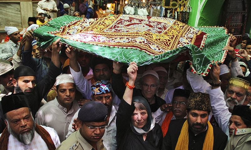 """People carry a holy """"Chaddar"""" (shawl) to offer it at the shrine of Muslim Sufi saint Khwaja Moinuddin Chishti during a Urs procession at Ajmer in the desert Indian state of Rajasthan April 20, 2015. — Reuters"""