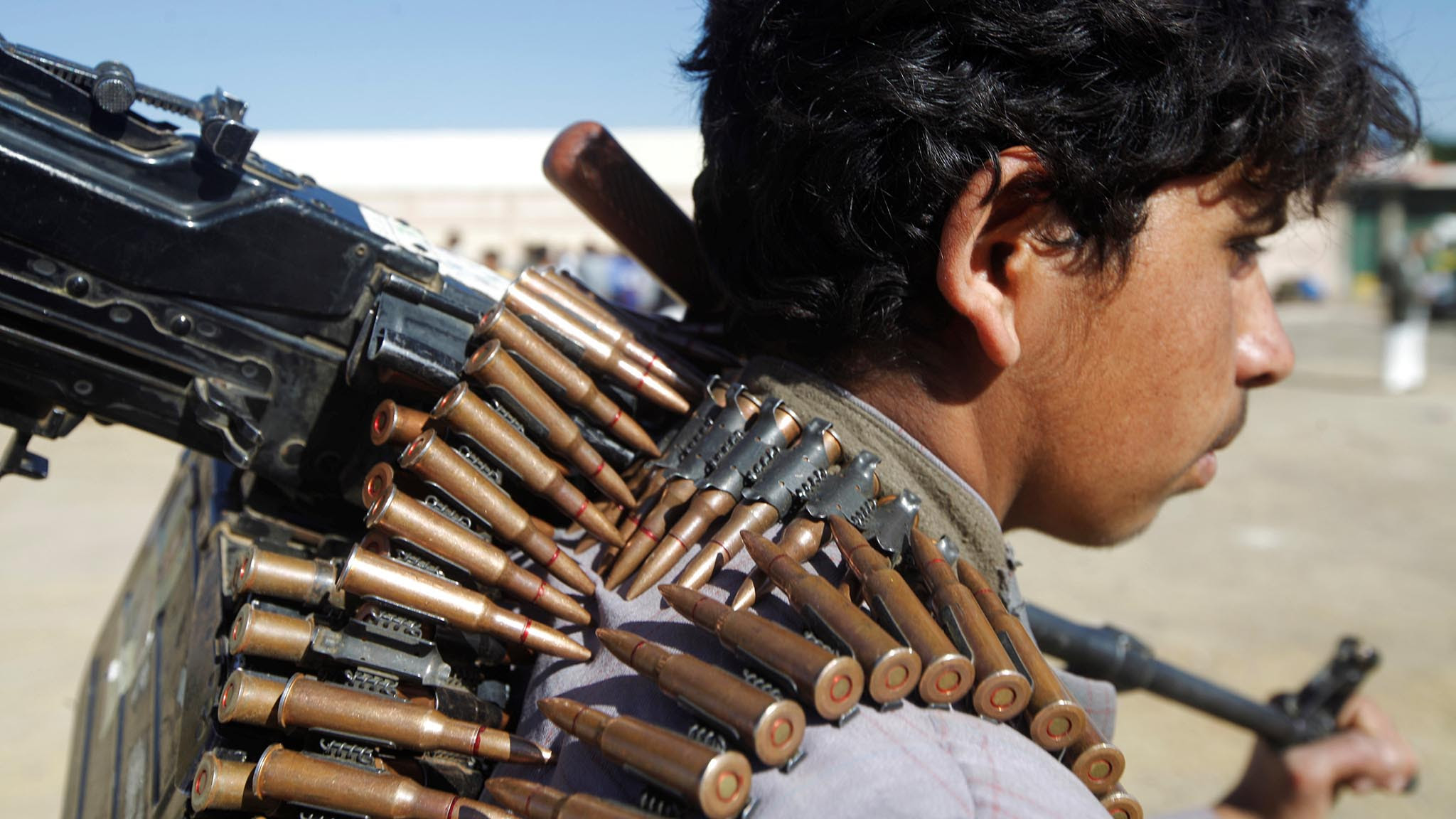 A Houthi rebel holds the barrel of a machine gun he carries during a rally held to mobilize fighters for battles against government forces, in Sanaa, Yemen
