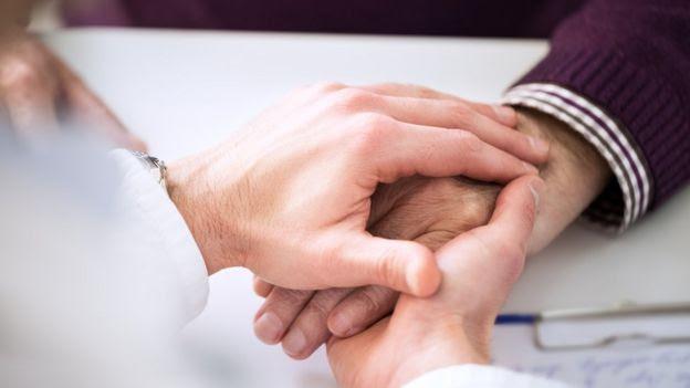 Mãos de profissional da saúde com a de um paciente
