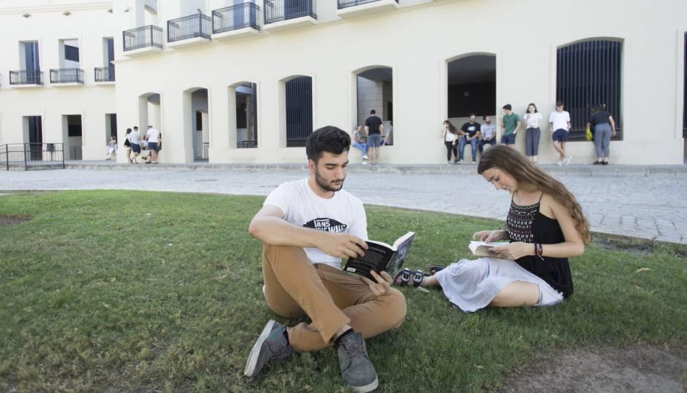 Dos estudiantes leen en uno de los jardines de la Facultad de Derecho de la Universidad de Sevilla.