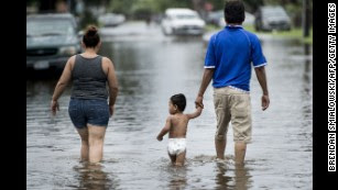 People walk through flooded streets as the effects of Hurricane Henry are seen on Saturday, August 26, in Galveston, Texas. Harvey made landfall shortly after 11 p.m. Friday, just north of Port Aransas, as a Category 4 storm and is being reported as the strongest hurricane to hit the United States since Wilma in 2005.