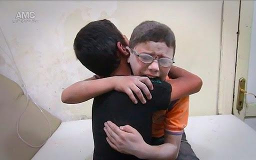 Dos chicos lloran desconsolados tras  la muerte de su hermano en Siria