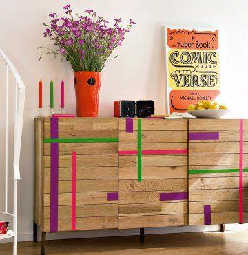 un meuble en bois décoré avec des rayures vertes, roses et violettes en gaffeur adhésif