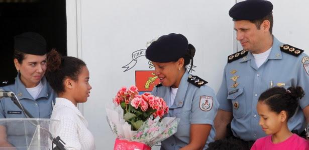 A major Pricilla de Oliveira Azevedo recebe flores de moradora da Rocinha em solenidade da troca de comando de 25 UPPs no Rio de Janeiro
