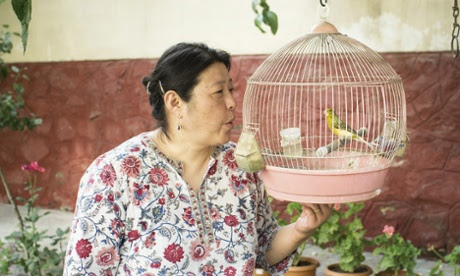 Hiromi Yasui in her garden with a bird in a cage