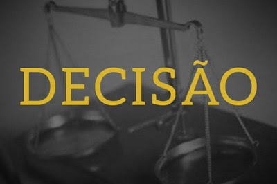"""Arte retangular mostra, ao fundo, foto de uma balança em preto e branco e, em primeiro plano, a palavra """"Decisão"""" escrita em letras amarelas."""