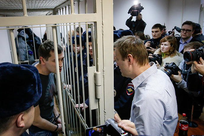Russian opposition leader and anti-corruption blogger Alexey Navalny (R) talks with his brother and co-defendant Oleg (inside defendants cage) during a court hearing in Moscow December 30, 2014 (Reuters / Sergey Karpukhin)