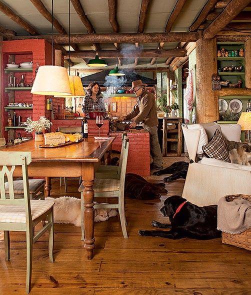 A cozinha rústica E o Lugar Preferido da casa de campo do Arquiteto Ernesto Tuneu e SUA Mulher, Mariah Villas Boas.  Com Fogão à lenha, ELA E Integrada à Sala de Jantar, Que segue o MESMO Estilo, com mesa de madeira de Demolição